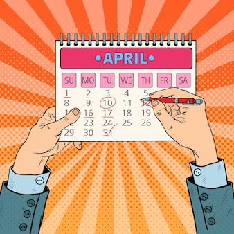 ポップアートのビジネスマン手計画カレンダーの日付。