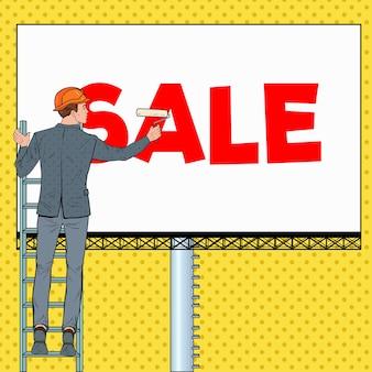 Pop art businessman in helmet with billboard. male worker applying sale banner. advertisement concept.