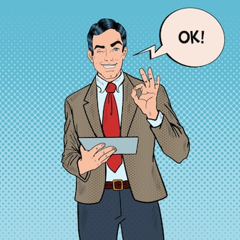 Pop art businessman with tablet gesturing ok and winking.  illustration