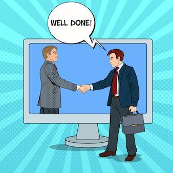 Pop art businessmen shake hands through the computer screen. business contract.