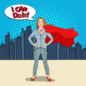 Поп-арт уверенная бизнес-леди супергерой в костюме с красной накидкой.