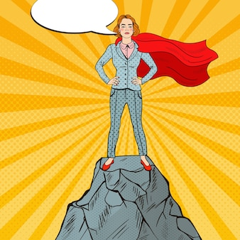 Pop art confident business woman super hero in suit with red cape standing on the mountain peak.