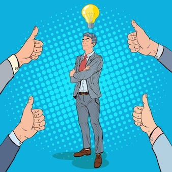 Pop art confident businessman with idea light bulb and hands showing thumbs up.