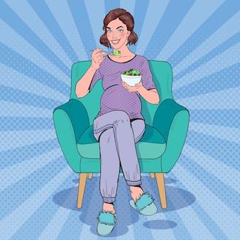 ポップアート幸せな妊娠中の女性が家でサラダを食べる