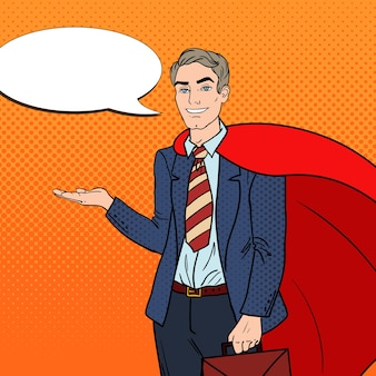 Pop art happy super businessman in red cape pointing on copy space
