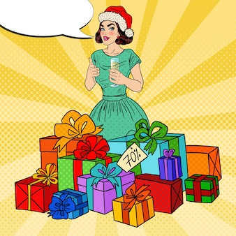 Поп-арт счастливая женщина в шляпе санты с большими подарочными коробками и бокалом шампанского.