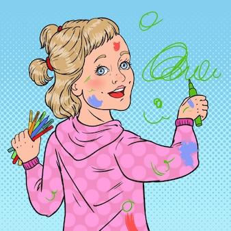 壁にポップアートの小さな画家の絵。壁紙にクレヨンで描く女の子。幸せな子供時代。