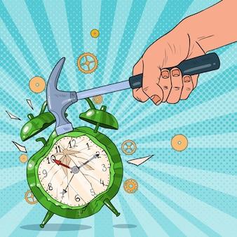 ハンマーを持って目覚まし時計を壊すポップアートの男性の手。