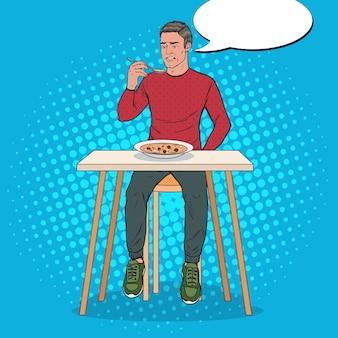 嫌な顔でスープを食べるポップアートの男。味のない食べ物。