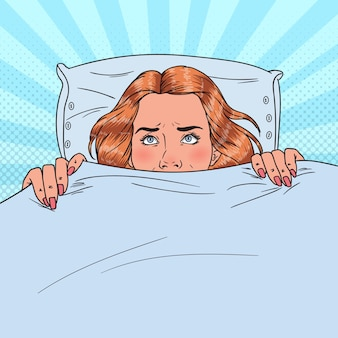 Pop art scared young woman hiding in bed. afraid girl under the blanket.