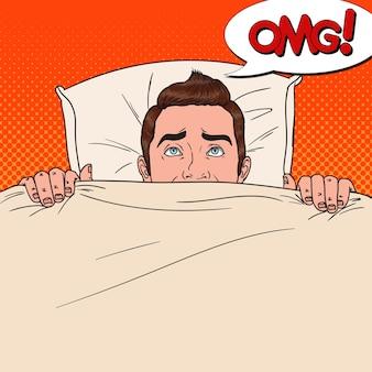 ベッドに隠れているポップアートショックを受けた男。怖い男は毛布の下でのぞきます。