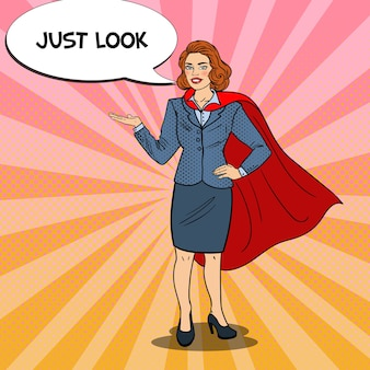 Pop art smiling super business woman in red cape pointing on copy space