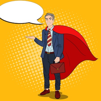 Pop art smiling super businessman in red cape pointing on copy space