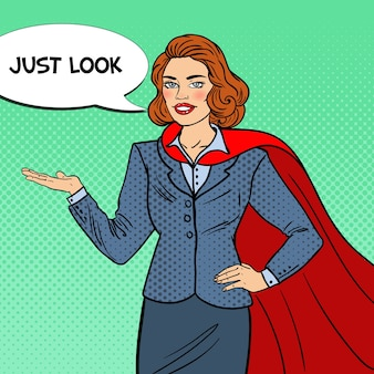 Pop art smiling super businesswoman in red cape pointing on copy space