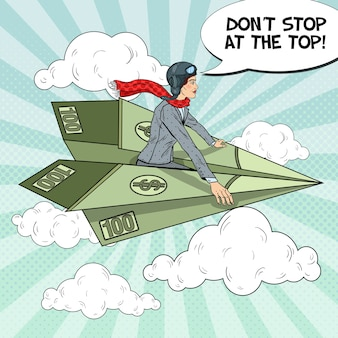 Pop art successful business woman flying on dollar paper plane.