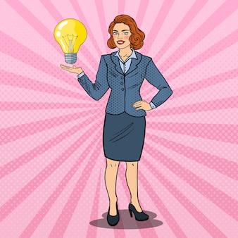 Поп-арт успешная деловая женщина с лампочкой творческой идеи