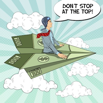 Pop art successful businessman flying on dollar paper plane.