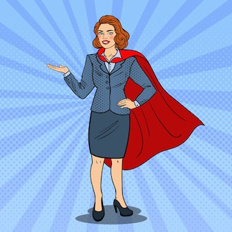 Pop art super business woman in red cape pointing on copy space