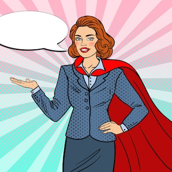 Pop art super businesswoman in red cape pointing on copy space