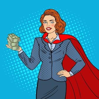 Pop art super businesswoman in red cape with money
