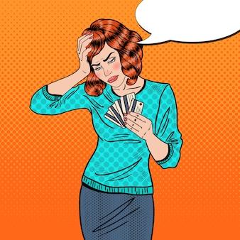 신용 카드를 가진 팝 아트 화가 여자는 두통이 있습니다.