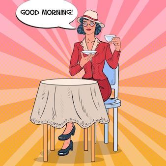 Pop art woman drinking tea in cafe