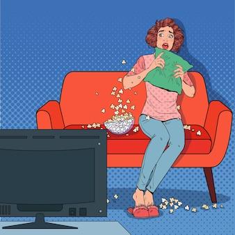自宅でホラー映画を見ているポップアートの女性。ポップコーンとソファでショックを受けた女の子の時計の映画。