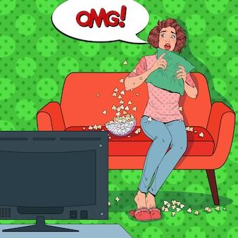 自宅でホラー映画を見ているポップアートの女性。ポップコーンと一緒にソファでおびえた女の子の時計の映画。