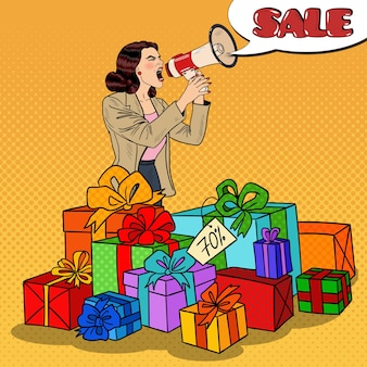 Pop art woman with megaphone promoting big sale standing in gift boxes.  illustration