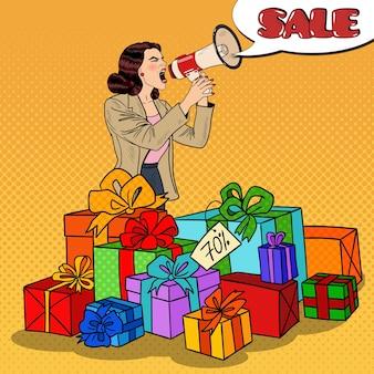 ギフトボックスに立っている大きな販売を促進するメガホンを持つポップアート女性。図