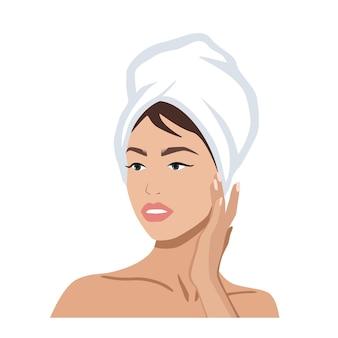 Портрет красивой женщины с полотенцем на голове, касающейся ее лица