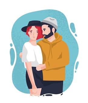 Портрет очаровательны мужчины и женщины в модных нарядах, стоя вместе и обнимающихся.