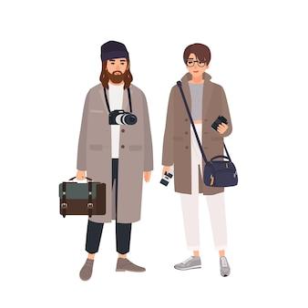 男性カメラマンと白い背景で隔離のコートで彼の女性アシスタントの肖像画。