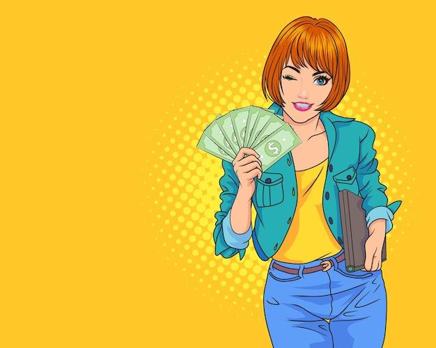 私たちにドル紙幣を見せてお金のフリーランサーを指しているポジティブな女性