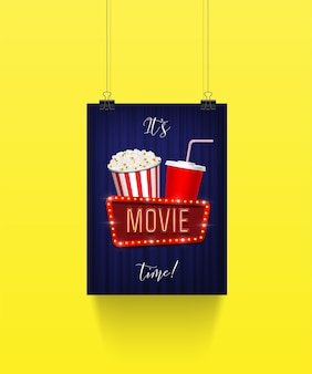 Poster hanging on paper clips with pop corn bucket and soda cup with movie sign