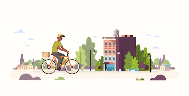 Postman in uniform riding bicycle carrying cardboard parcel box   courier cycling outdoors express delivery service concept modern cityscape background  full length horizontal