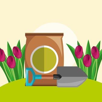 Potting soil shovel and red tulips flowers garden