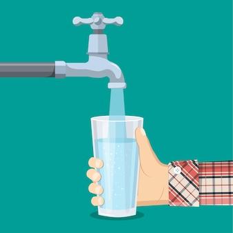 수도꼭지에서 유리 잔에 물을 붓습니다. 손에 들고 정화 물 컵