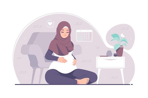 彼女の腹に優しく触れる妊娠中のイスラムのヒジャーブの女の子