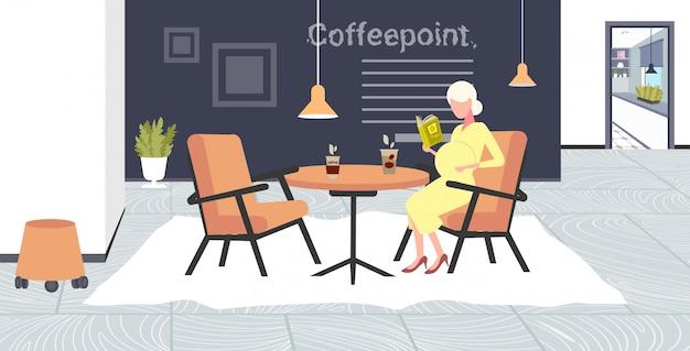 Беременная женщина чтение книги сидя в кафе стол девушка касаясь ее живот беременность и материнство концепция современный точка кофе интерьер полная длина горизонтальный