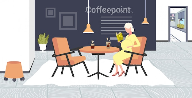 Pregnant woman reading book sitting at cafe table girl touching her belly pregnancy and motherhood concept modern coffee point interior  full length horizontal