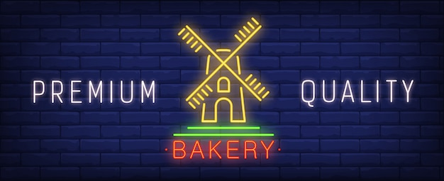 Premium quality bakery neon sign. windmill and bright inscription on brick wall background