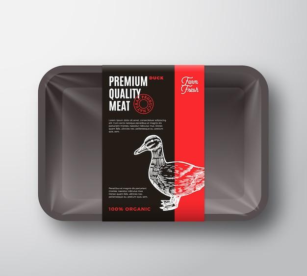 プレミアム品質の鴨肉パッケージとラベルストライプ。セロハンカバーが付いている食糧プラスチック皿の容器。パッケージレイアウト。現代のタイポグラフィと手描きのアヒルのシルエットの背景。
