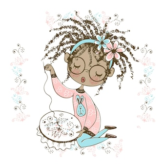 A pretty black girl is engaged in needlework and embroiders a beautiful pattern on the hoop.