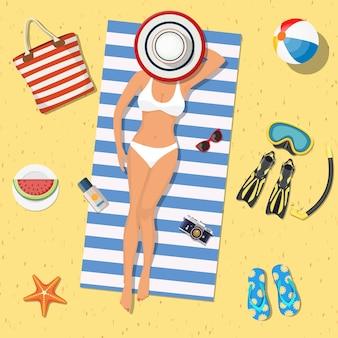 かわいい女の子がビーチに横たわっています。ビキニを着たビーチの女の子。
