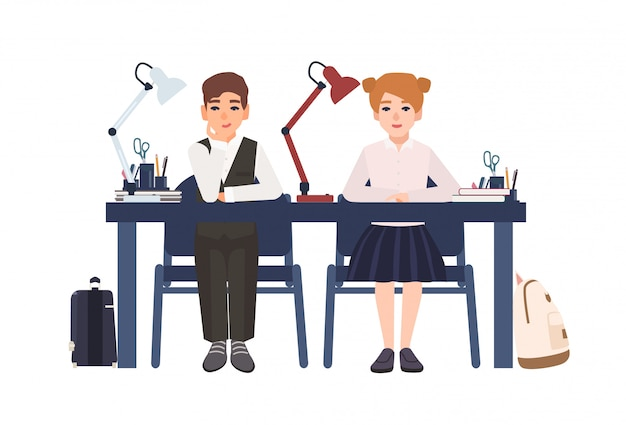Primary school boy and girl in uniform sitting at desk in classroom isolated