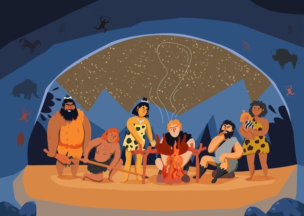 Famiglia di uomini primitivi che cucina carne sul fuoco in un cartone animato della grotta