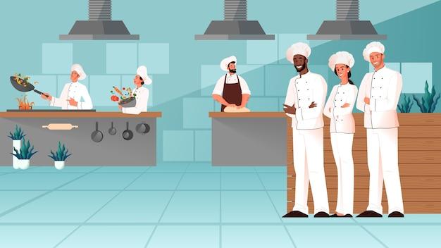レストランのキッチンで一緒に立っているプロのシェフ。エプロンで調理するレストランのスタッフ。食品プロセスの準備。カフェキッチンインテリア。