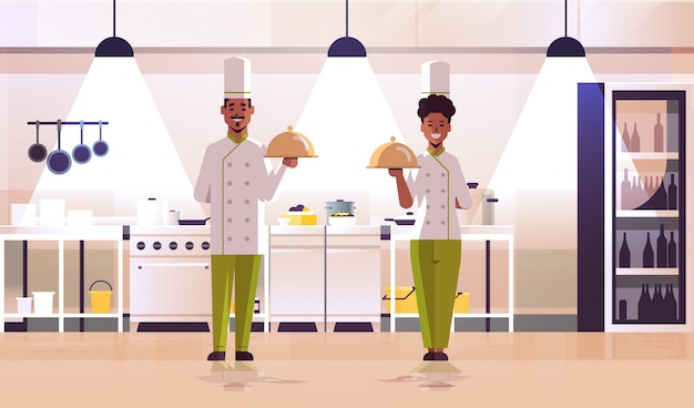 Professional chefs couple holding covered platters serving trays african american woman man in uniform standing together cooking food concept modern kitchen interior