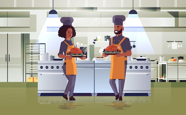 Professional chefs couple holding trays with roasted chicken man woman in uniform carrying thanksgiving turkey cooking food concept modern restaurant kitchen interior